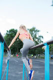 Sexy young fitness girl pulls up on street sport gym. Blonde fitness woman in sport wear with perfect fitness body on street. Workout performing abdominal Royalty Free Stock Images