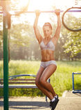 Sexy young fitness girl pulls up on street workout. Sexy young fitness girl pulls up on street sport gym. Brunette fitness woman in sport wear with perfect Stock Photography