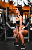 Beautiful sporty sexy woman doing squat workout in gym stock photos