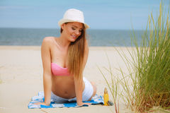 Sexy young girl on beach. Sun protection concept. Attractive sexy long haired woman in straw hat lying on beach with sunscreen body lotion and sunglasses Royalty Free Stock Photography