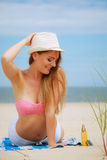 Sexy young girl on beach. Sun protection concept. Attractive sexy long haired woman in straw hat lying on beach with sunscreen body lotion and sunglasses Royalty Free Stock Images