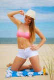 Sexy young girl on beach. Sun protection concept. Attractive sexy long haired woman in straw hat on beach with sunscreen body lotion and sunglasses Royalty Free Stock Photography