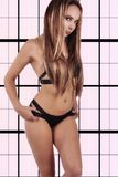 Sexy young girl in a black bathing suit on an abstract backgroun Royalty Free Stock Image
