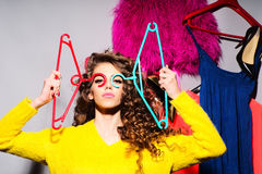 Sexy young girl with clothes. Sexy young girl with curly hair in yellow sweater holding hangers standing amid colorful clothes pink red blue colors on grey wall Stock Images