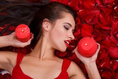 A sexy girl lies in the rose petals, holds two burning candles and looks away. A sexy young girl with dark long hair lies in the red rose petals, holds in her Royalty Free Stock Images