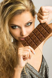 Sexy young girl with delicious milk chocolate. Close-up studio portrait of a beautiful young woman eating chocolate Royalty Free Stock Images