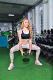 young girl doing squats exercises with dumbbells. Fitness woman workout in gym royalty free stock photos