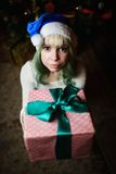 Sexy young girl gives gift under Christmas tree Royalty Free Stock Photo