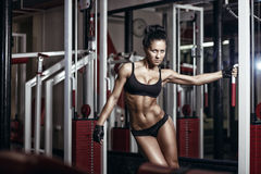 Sexy young girl in the gym holding on training machine. Stock Image