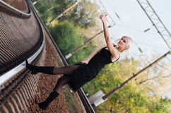 Sexy young girl is hitchhiking on a railroad. Sexy young girl in black dress is hitchhiking on a railroad Royalty Free Stock Photography