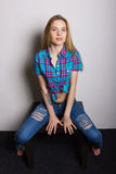 Sexy young girl in jeans and a plaid shirt posing sitting on the coffee table Royalty Free Stock Photos