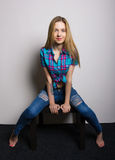 Sexy young girl in jeans and a plaid shirt posing sitting on the coffee table Stock Photos