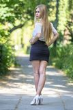Sexy young girl in miniskirt. Very sexy blonde girl in black miniskirt and high heels Stock Image
