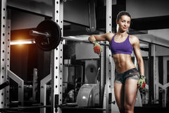 Sexy young girl resting after squat exercises. Fitness brunette Stock Photos