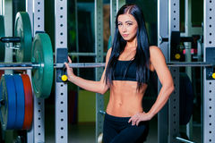 Sexy young girl resting after squat exercises. Fitness brunette woman.  Royalty Free Stock Photos