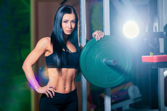 Sexy young girl resting after squat exercises. Fitness brunette woman.  Royalty Free Stock Image