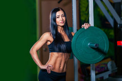 Sexy young girl resting after squat exercises. Fitness brunette woman Stock Images
