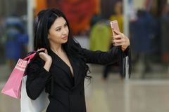 Sexy young girl with shoppping bags using her smartphone to take a selfie photo in mall. Sexy young girl with shoppping bags using her smartphone to take a Stock Photo