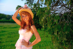 Sexy young girl smiling on sunset green background. Sexy young girl smiling, dressed in a pink dress and wearing a hat Stock Image