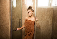 Sexy, young girl takes a shower in the bathroom on a brown tile background. The attractive woman is wrapped in a brown towel. A beautiful, slender and cute Royalty Free Stock Photo