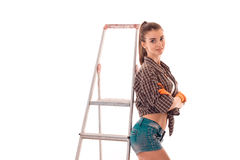 Sexy young girl in uniform makes renovation isolated on white background. Sexy young girl in uniform makes renovation isolated on white Royalty Free Stock Photography