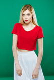Young Girl Wearing Red Top and White Skirt is Posing on Green Background. Portrait of Sensual Pretty Blonde in royalty free stock photos