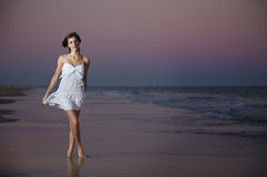 Sexy young girl in a white suit. On the beach at sunset Stock Image