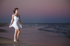 Sexy young girl in a white suit. On the beach at sunset Royalty Free Stock Photo