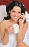 Sexy young Hispanic woman on bed drinking coffee Royalty Free Stock Image