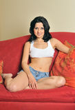 Sexy young Hispanic woman on couch Royalty Free Stock Image