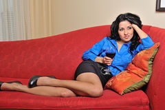 Sexy young Hispanic woman on couch with wine Royalty Free Stock Photo