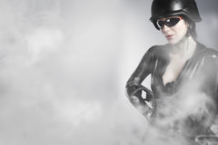 Sexy young holding gun with smoke Stock Images