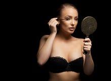 young lady applying mascara on eyelashes Stock Photo