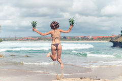 Sexy young lady in bikini jumping on the beach with fresh raw healthy pineapple fruit. Happy vacation concept. Bali. Royalty Free Stock Images