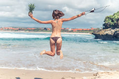 Sexy young lady in bikini jumping on the beach with fresh raw healthy pineapple fruit. Happy vacation concept. Bali. Royalty Free Stock Photo