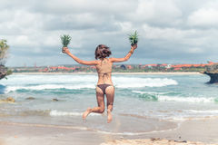 Sexy young lady in bikini jumping on the beach with fresh raw healthy pineapple fruit. Happy vacation concept. Bali. Stock Image