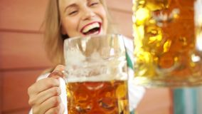 A young lady drinks beer at a beer festival in Germany. Close-up, large beer mugs, a girl laughing cheerfully, red. Lips, white-toothed smile stock video footage
