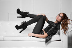 Sexy young lady. Wearing black fashionable clothes and high heels lying on the sofa Stock Photos