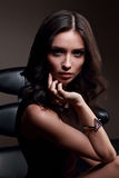 Sexy young makeup model with vamp look posing on dark shadow bac. Kground in fashion trendy watch on the hand Stock Photos