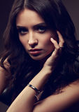 Sexy young makeup model with vamp look posing on dark shadow background. In fashion trendy watch on the hand Stock Photo