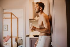Young man with bare torso holding hand orange juice, looking out the window and smiling while standing in kitchen. At home royalty free stock photo
