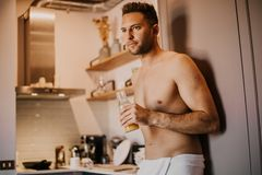 Young man with bare torso holding hand orange juice, looking out the window and smiling while standing in kitchen. At home stock photo