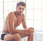 Sexy young man. In black briefs is looking a camera in dismay while sitting on bed Stock Images