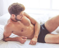 Sexy young man. In black briefs is lying in bed Stock Photos