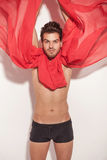 Sexy young man fluttering a red scarf Stock Images