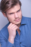 young man with hand on his chin Stock Photo