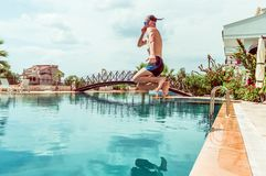 Sexy young man jumping in the swimming pool in a resort. Sexy fit man jumping in the swimming pool in a resort Royalty Free Stock Photos