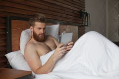 young man is lying in bed with tablet in hands royalty free stock image