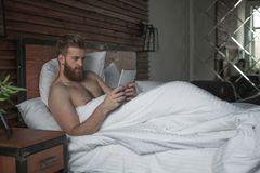 young man is lying in bed with tablet in hands stock image
