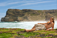 Sexy young man relaxing on rocks Royalty Free Stock Image